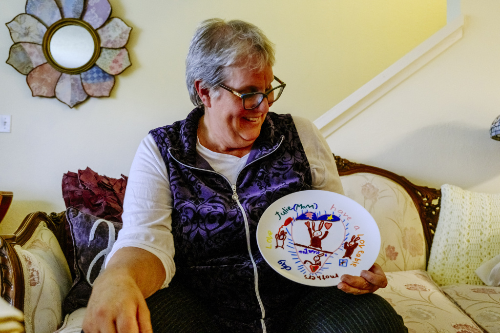 Audrey Woolfolk holds a plate that Julie decorated for a Mother's Day gift when she was younger.