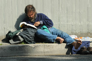 File photo: An unemployed and homeless man reads a bible near a freeway exit in Los Angeles on March 6, 2009.