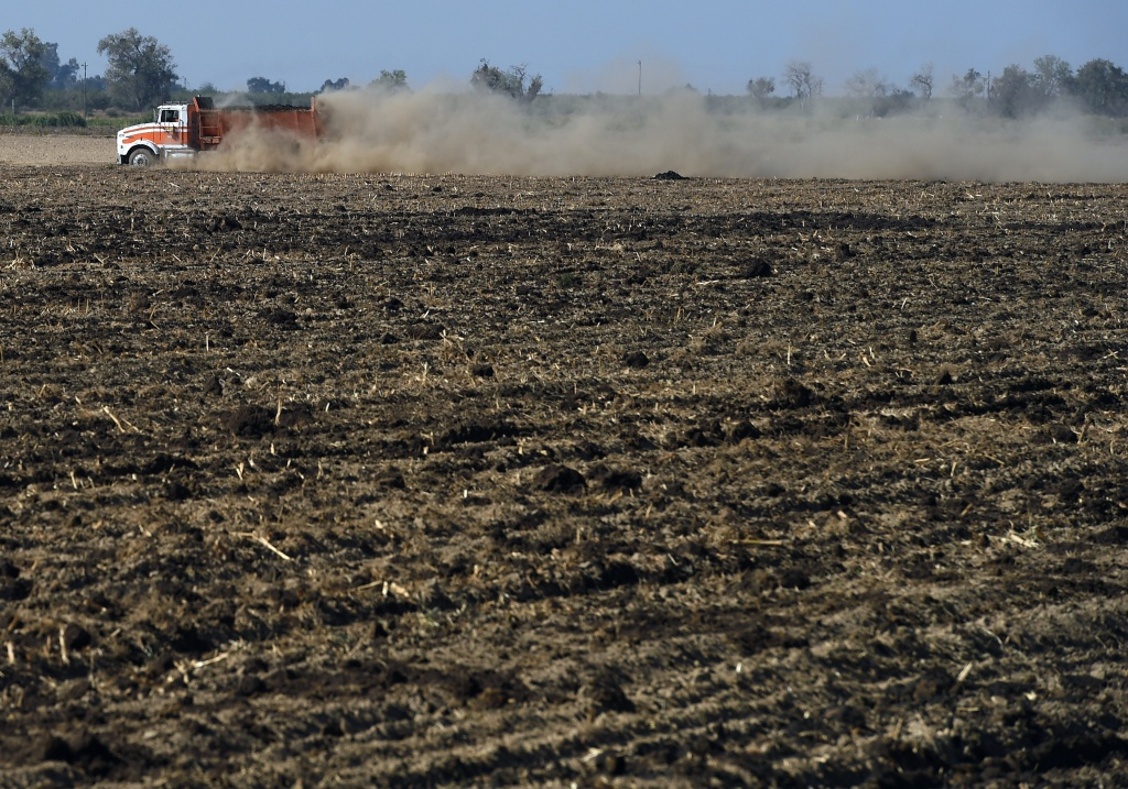 A vehicle raises a large dust cloud as it drives on a parched farm field in Los Banos, California.