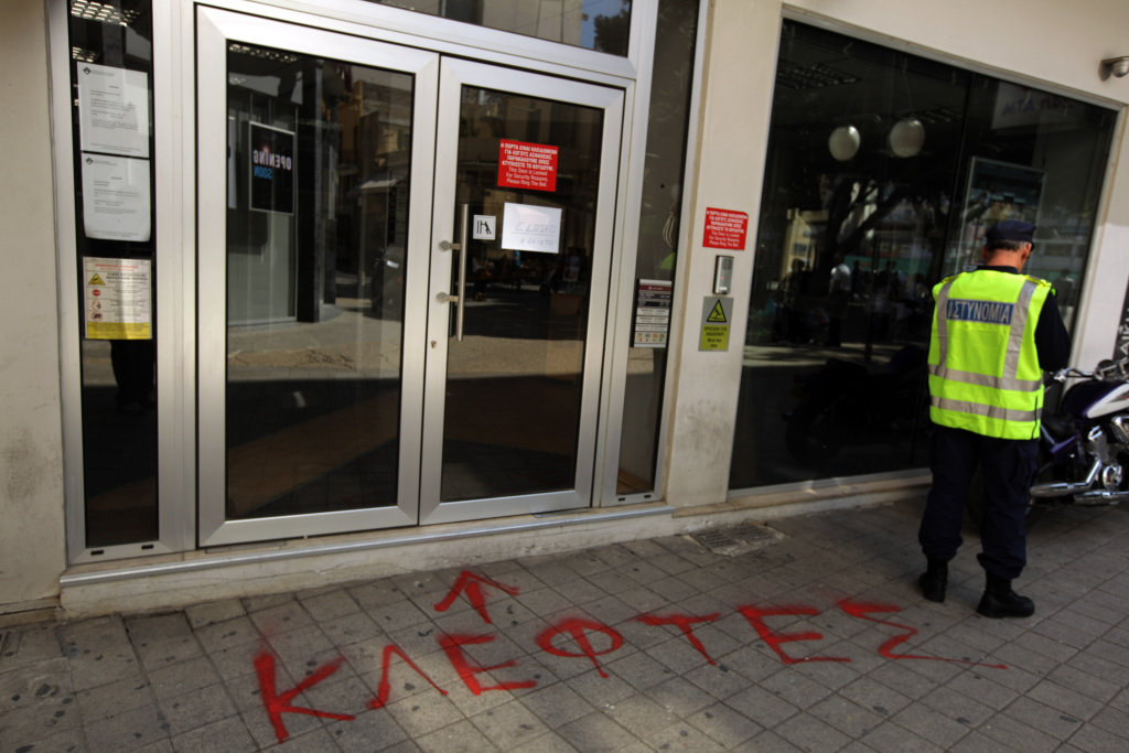 A Cypriot policeman stands next to graffiti in Greek reading 'Thieves' at the entrance of closed branch of the Laiki (Popular) Bank in central Nicosia on March 20, 2013.