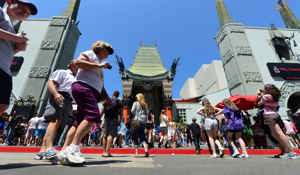 Tourists walk past the TCL Chinese Theater, formerly known as Grauman's Chinese Theater and Mann's Chinese Theater, on August 7, 2013 along Hollywood Boulevard.