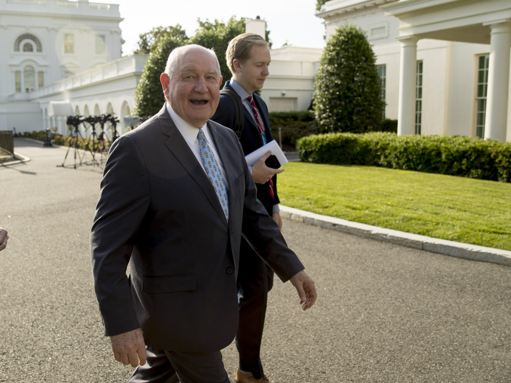 Agriculture Secretary Sonny Perdue announced on Thursday $16 billion in aid to help farmers hurt by the ongoing U.S.-China trade dispute. Here, Perdue walks past the West Wing of the White House.