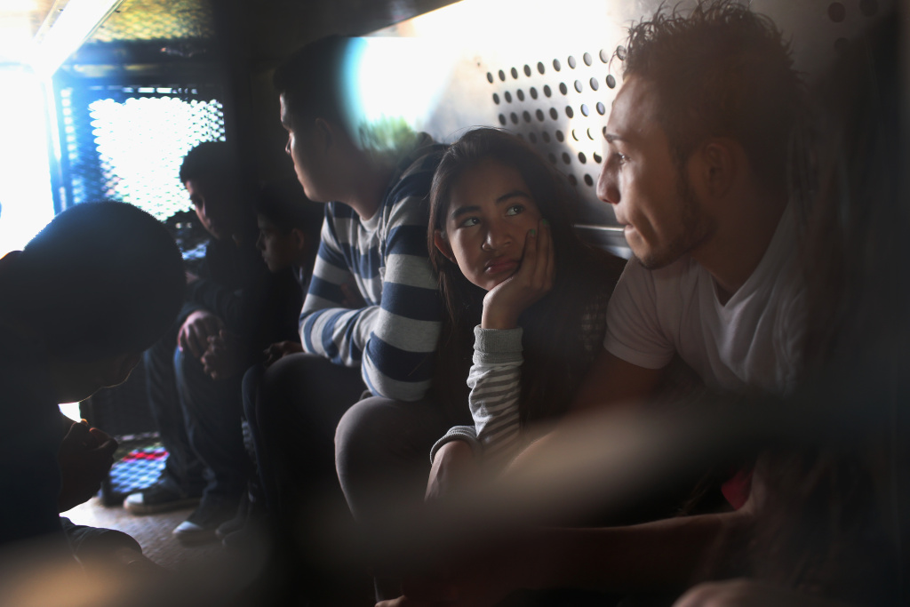 Central American immigrants wait to be transported after turning themselves in to U.S. Border Patrol agents.