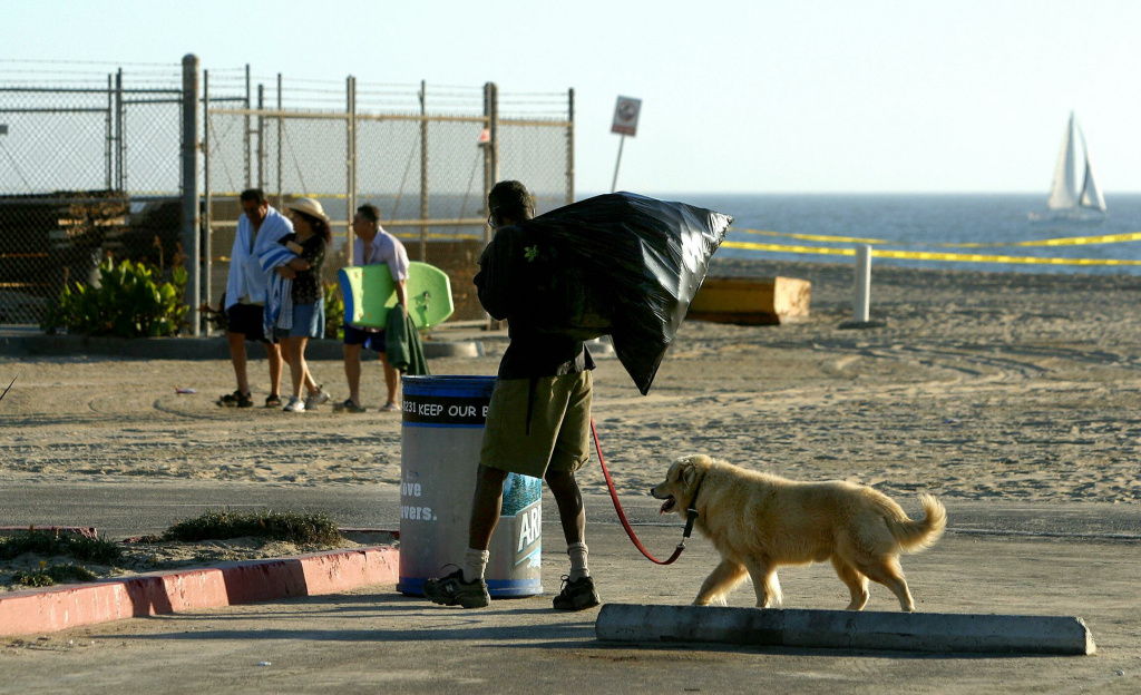 A homeless man with his dog stops at a trash bin to search for recyclable cans as beach-goers head home for the day at Venice Beach in Los Angeles, California, 28 August 2003.