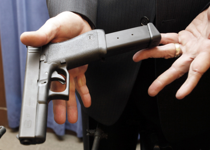 Los Angeles Police Chief Charlie Beck displays a handgun loaded with an extended clip on Wednesday March 2, 2011, during a news conference in Los Angeles. Chief Beck endorsed a proposed federal ban on the sale of high-capacity ammunition magazines that have been used in mass shootings.