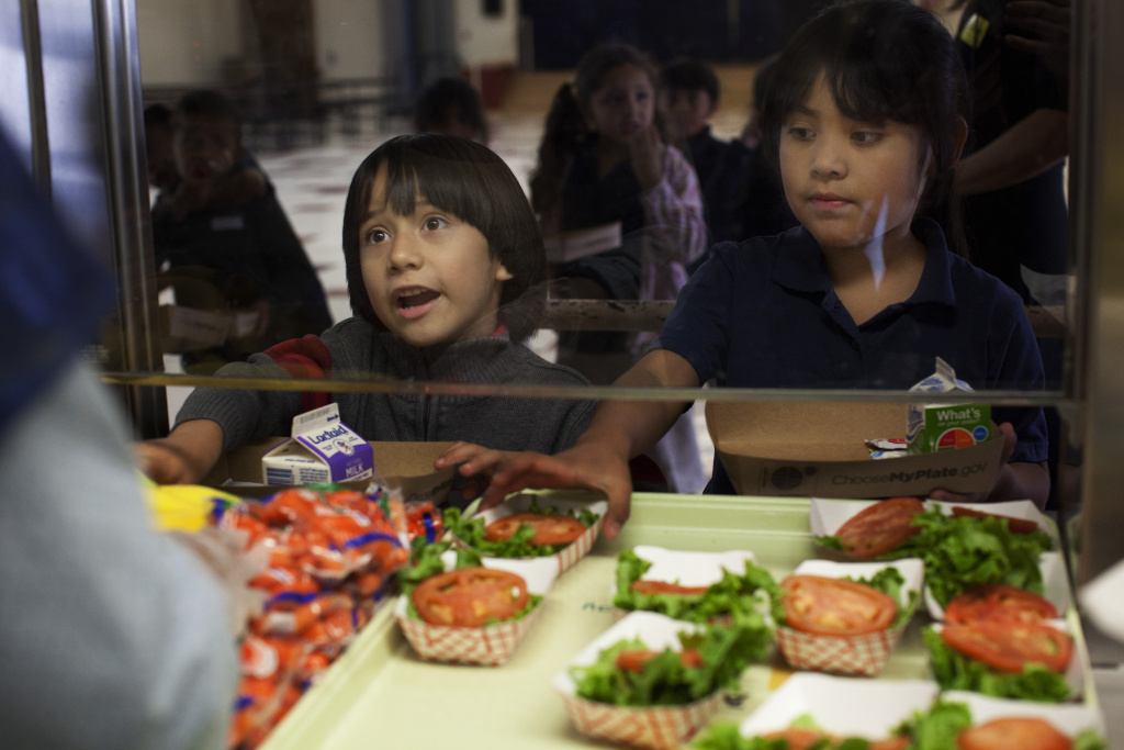 Carlos Castro, left, and Michele Canete go through the lunch line at Gratts Learning Academy for Young Scholars in Los Angeles.