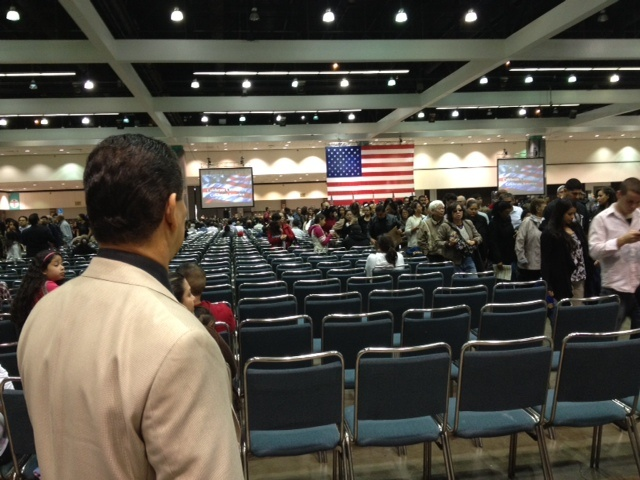 A newly naturalized U.S. citizen looks around minutes after he was sworn in and as the room begins to clear.
