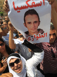 Activists carry a poster with pictures of Khaled Said during an anti-government protest in Cairo, Egypt, on June 20. Said was allegedly beaten to death by two plainclothes policemen on an Alexandria street.