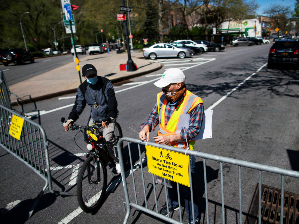 A New York City worker closes a street to car traffic in Manhattan on Saturday so that pedestrians and cyclists can maintain social distancing. Mayor Bill de Blasio said 100 miles will be closed to car traffic in the coming weeks.
