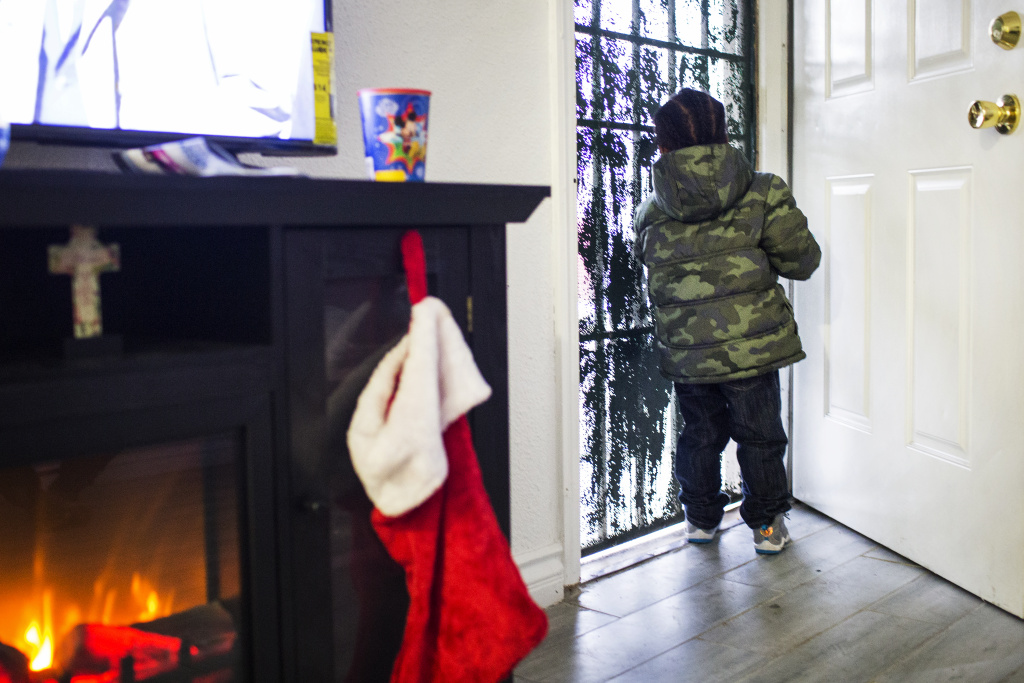 Tandra Dixon's two-year-old son, J.J., looks out the front door of their South Los Angeles home on Wednesday afternoon, Dec. 21, 2016. In November, Dixon and her five children moved into this two-bedroom apartment.