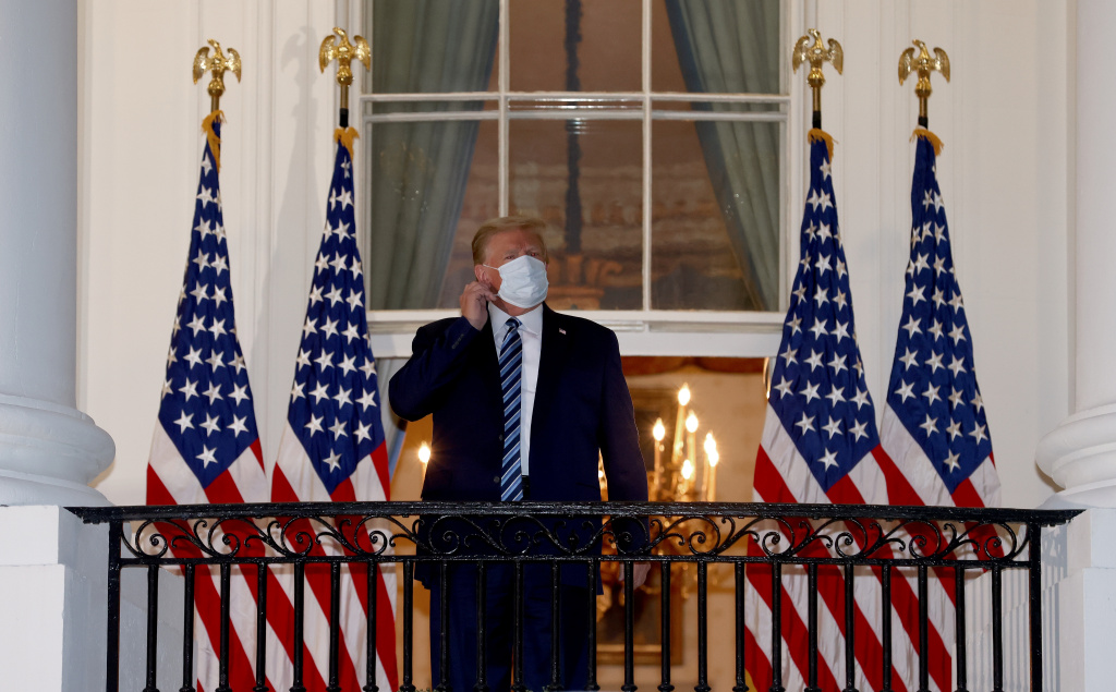 U.S. President Donald Trump reaches to remove his mask upon return to the White House from Walter Reed National Military Medical Center in Washington, DC.