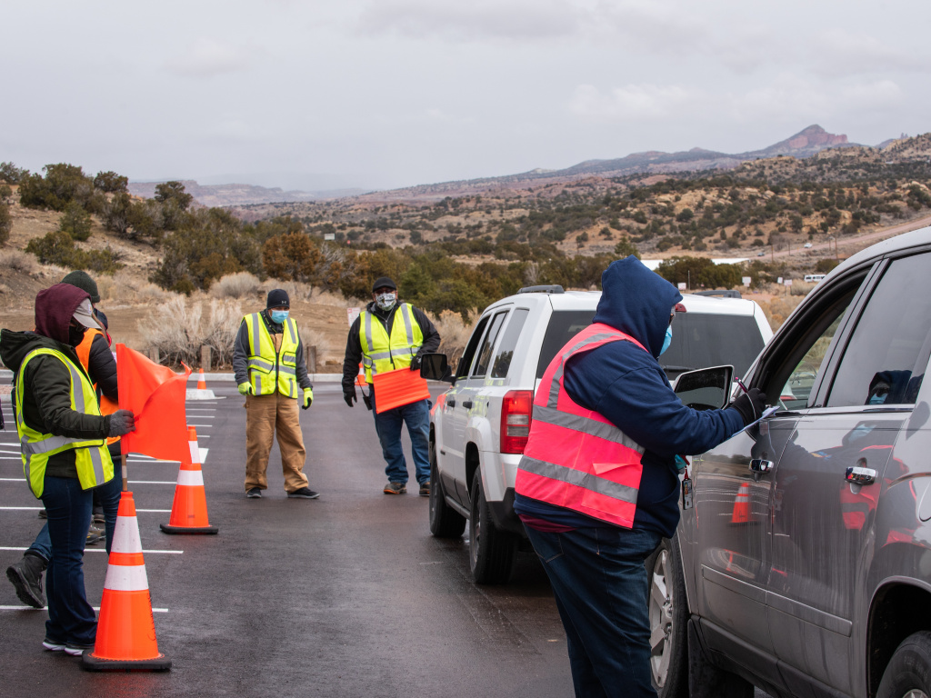Workers greet arrivals at a drive-in vaccination site at University of New Mexico's Gallup campus in Gallup, N.M., on March 23. The Navajo Nation has vaccinated more than half of its adult population, outpacing the U.S. national rate.