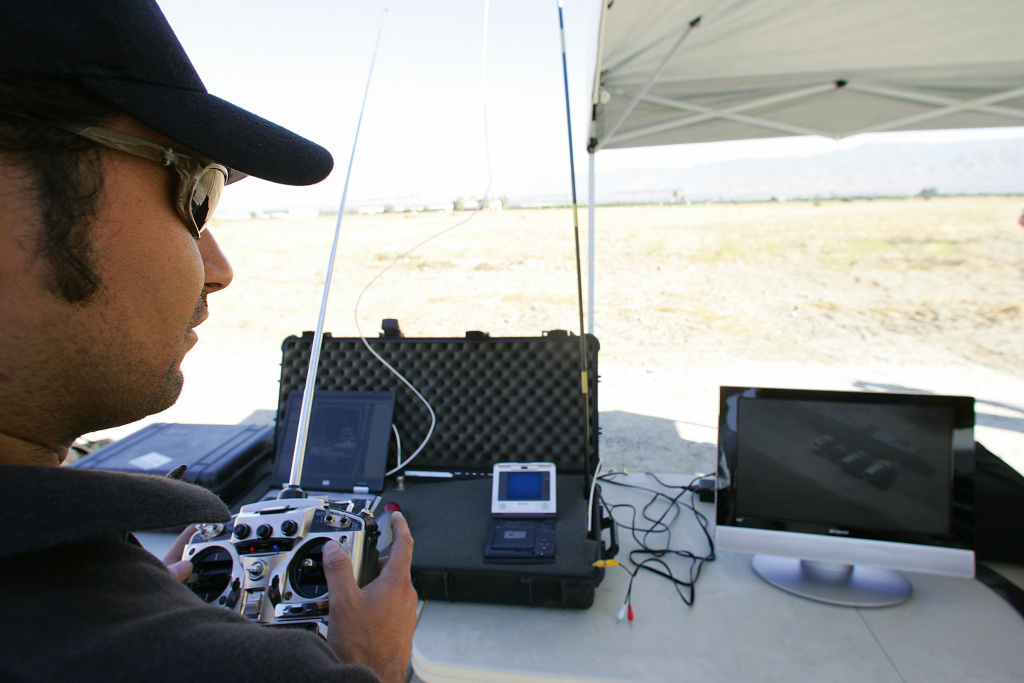 SkySeer designer Victor Torres flies the Skyseer Unmanned Arial Vehicle (UAV) drone (not in photo) with its remote control device (in hand) as he watches the live video images transmitted from the drone overhead to his video monitor (at left), 16 June 2006 at a demonstration in Redlands, CA.