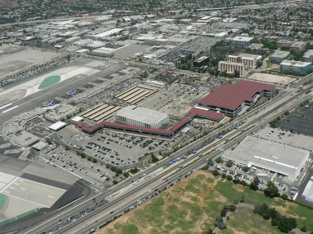 This aerial view shows the red-roofed Regional Intermodal Transportation Center that will connect air terminals of Bob Hope Airport at left, a new rental car center. Eventually, the walkway will also connect to the train platforms, seen lower right.