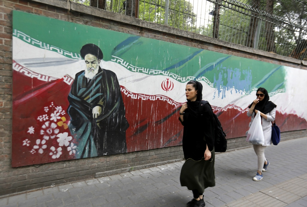 An Iranian woman walks past a mural on the wall of the former US embassy in the Iranian capital Tehran on May 8, 2018.