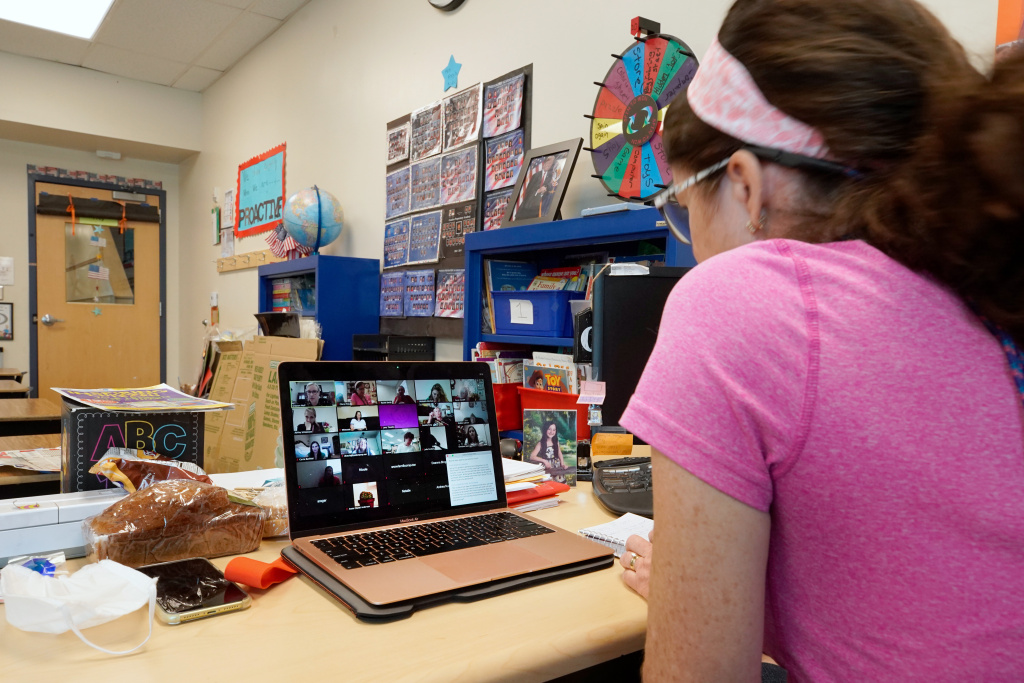 A teacher participates in a school Zoom meeting, to social distance.