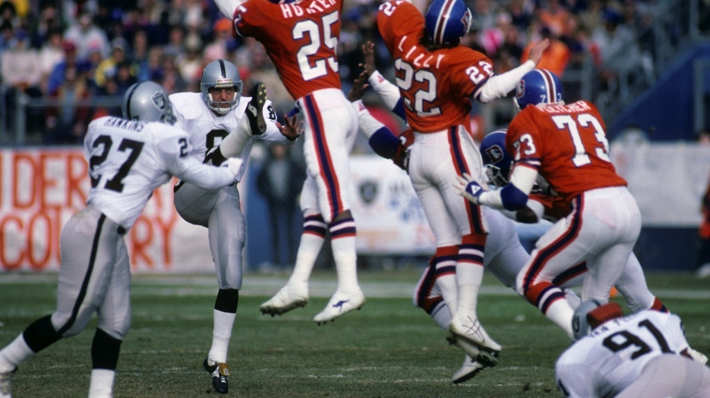 Punter Ray Guy, No. 8 of the Los Angeles Raiders, kicks the ball past the Denver Broncos' rush during a 1985 game.