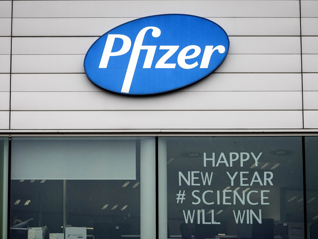 A sign is shown in the window of an office at Pfizer Manufacturing in Puurs, Belgium, on Monday, the same day the European Medicines Agency authorized the use of the company's COVID-19 vaccine.
