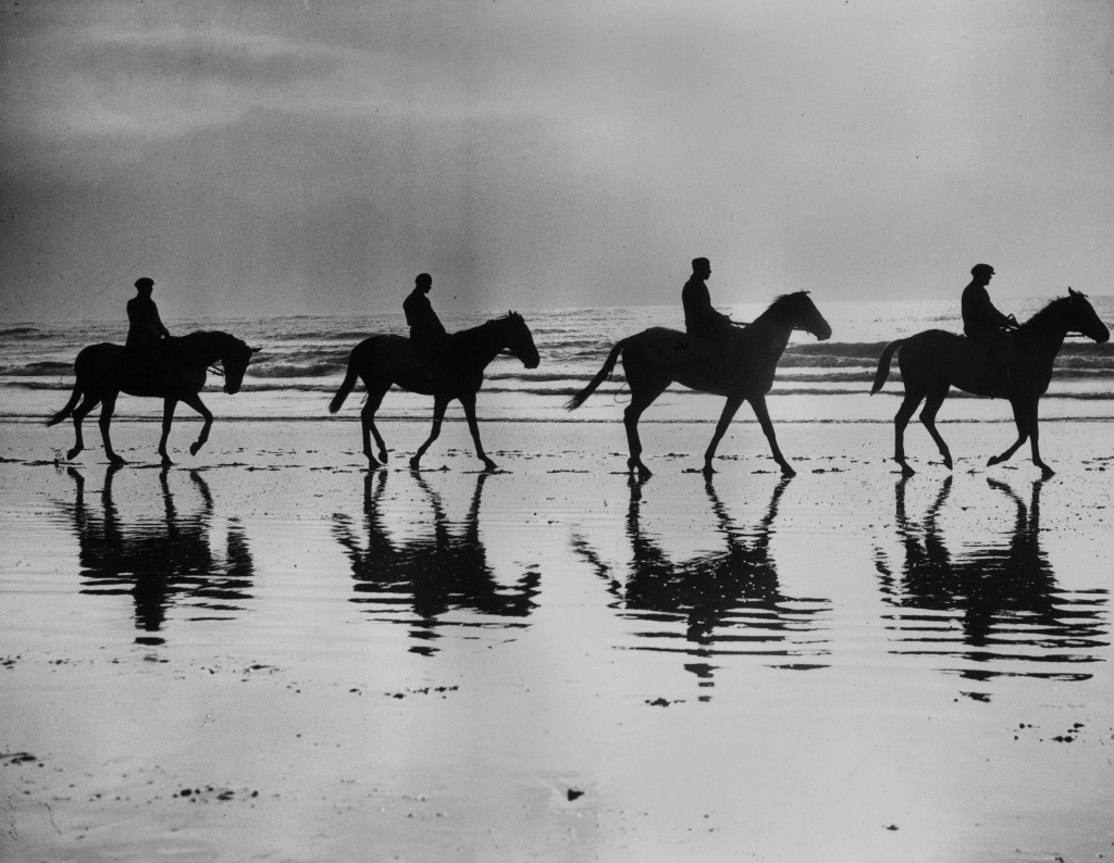 14th February 1938: Racehorses being trained by David Dale are silhouetted against the skyline as they walk along the beach at Newhaven, Sussex. David Dale believes in sea water to strengthen their legs. Left to right; Ontario II, Tabrian II, Serpentare and Irish Challenge. (Photo by Reg Speller/Fox Photos/Getty Images)