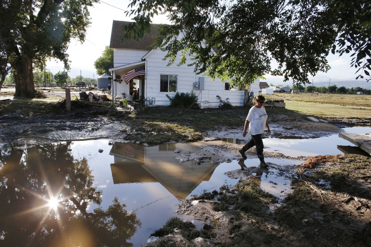 Local resident Sue Sadar walks across a trench of mud which used to be a lawn as she and family members clean property in an area inundated in flooding, in Hygiene, in Boulder County, Colo., Monday Sept. 16, 2013. Searches continue for missing people in isolated Colorado mountain towns.