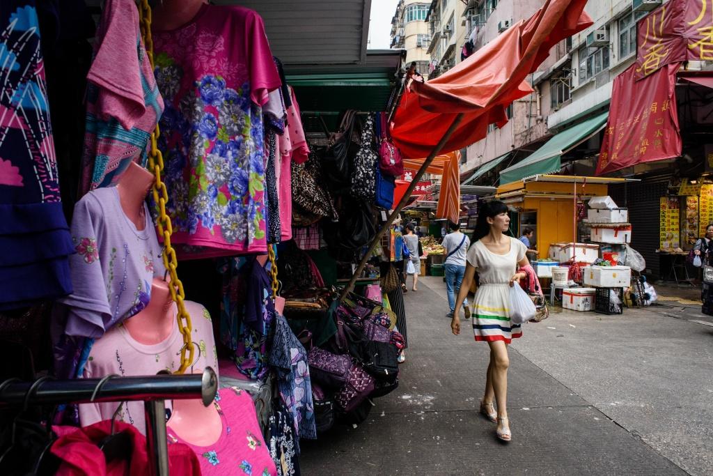 A woman walks past a street market stall in Hong Kong.