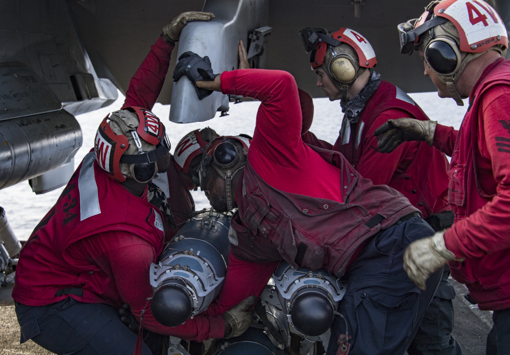 "(Feb. 21, 2018) Sailors attach ordnance to an F/A-18C Hornet assigned to the ""Blue Blasters"" of Strike Fighter Squadron (VFA) 34 on the flight deck of Nimitz-class aircraft carrier USS Carl Vinson (CVN 70)."