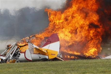 Flames erupt from a plane after it crashed at the Vectren Air Show at the airport in Dayton, Ohio. The crash killed the pilot and stunt walker on the plane instantly, authorities said.