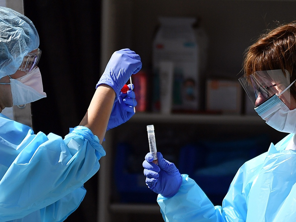 Medical workers at Kaiser Permanente French Campus test a patient for the coronavirus disease COVID-19 at a drive-through testing facility in San Francisco on Thursday.