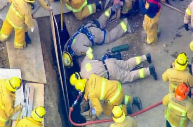 Rescuers attempted to retrieve a worker trapped in an 8-foot-deep trench on North Benedict Canyon Drive.