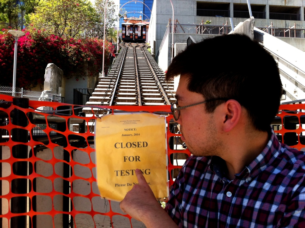 Los Angeles Downtown News reporter Eddie Kim points to the problem, as the two Angels Flight funicular railway cars hang in limbo at the top of the tracks to Bunker Hill.