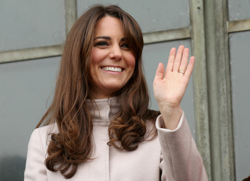 Catherine, Duchess of Cambridge smiles and waves to the crowds from the balcony of Cambridge Guildhall as she pays an official visit to Cambridge with Prince William, Duke of Cambridge on November 28, 2012 in Cambridge, England.