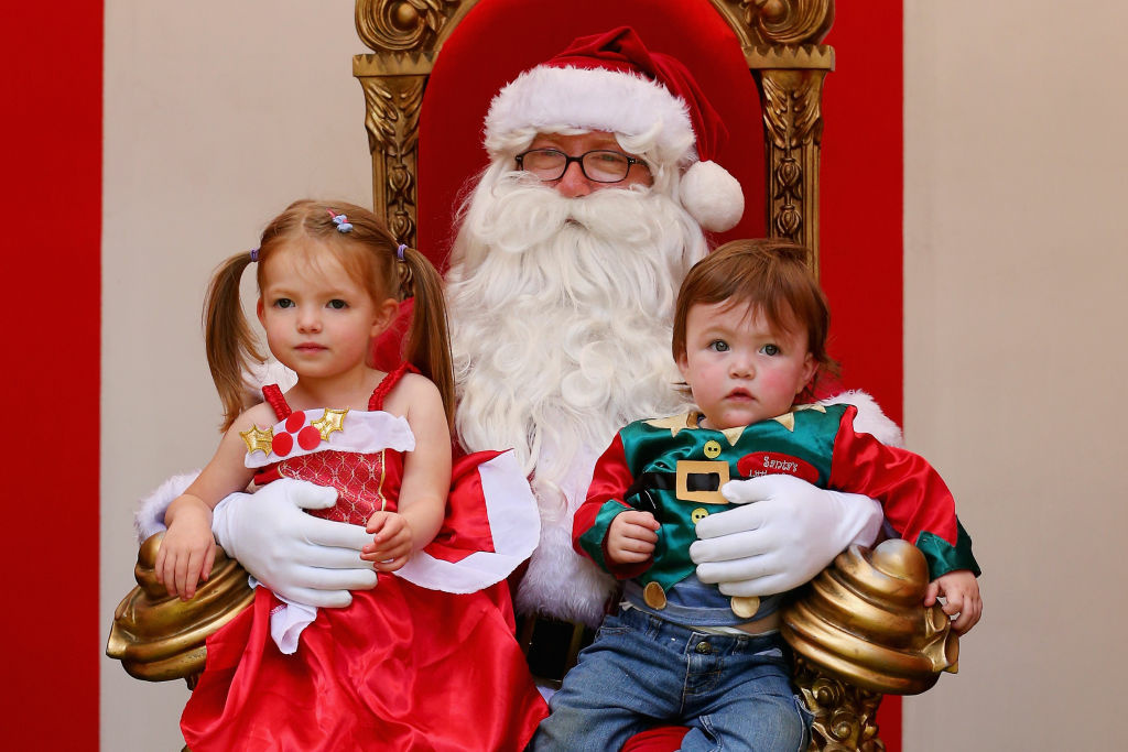 Children pose for a photo with Santa Claus as he visits Christmas Square on December 20, 2012 in Melbourne, Australia. Australian retailers are looking forward to an improved Christmas trading period when compared to recent years. Improved consumer confidence, interest rate cuts, and stabilising house prices point to a positive outlook for the current Christmas period.