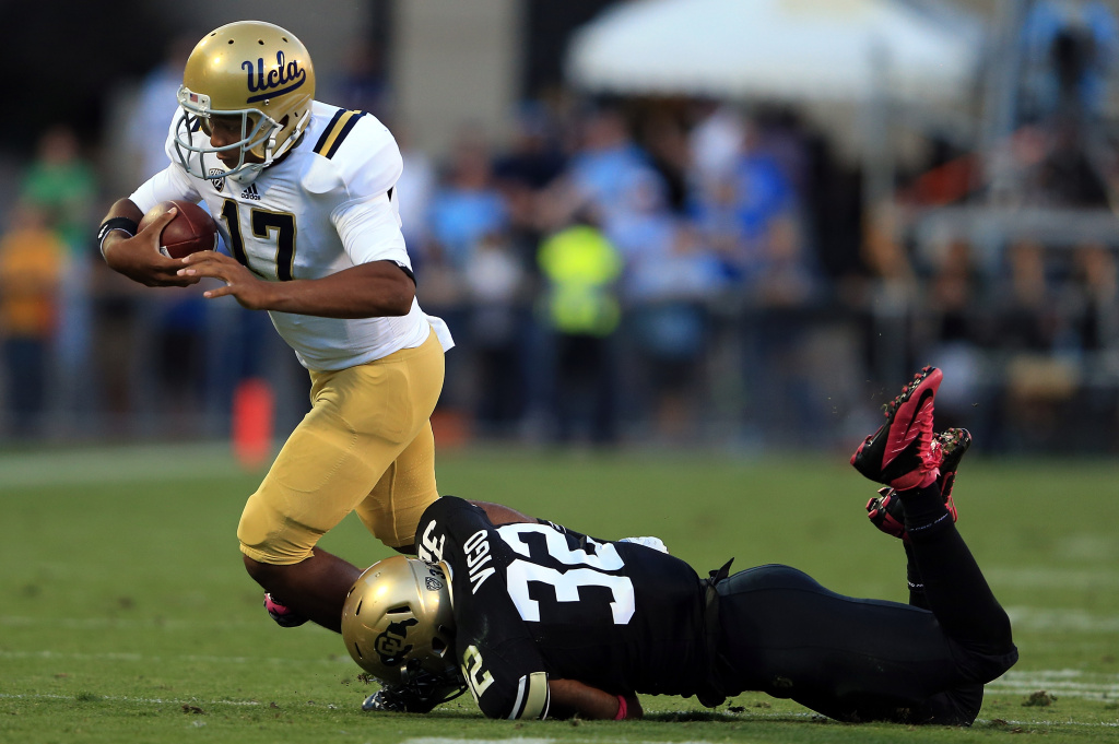 Quarterback Brett Hundley #17 of the UCLA Bruins is tackled by linebacker Paul Vigo #32 of the Colorado Buffaloes at Folsom Field on September 29, 2012 in Boulder, Colorado. UCLA defeated Colorado 42-14.