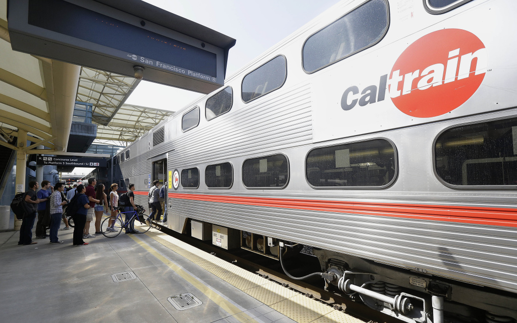 Commuters board a Caltrain train at the Caltrain and Bay Area Rapid Transit station in Millbrae, Calif.