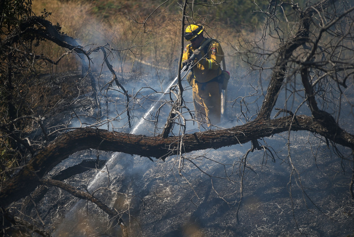 A firefighting helicopter prepares to drop water on a ridge while battling the Wragg Fire on July 23, 2015 in Winters, California. The fast moving Wragg Fire has burned more than 6,000 acres and threatens nearly 200 homes as it moves through dry brush near Lake Berryessa. Over 500 firefighters are fighting the blaze that is 5 currently percent contained.