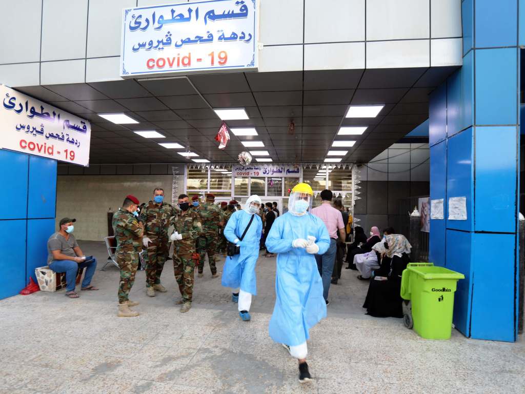 People wait for COVID-19 tests at a hospital in Baghdad on June 4.