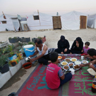 Syrian refugees break their fast outside their tent at a Syrian refugee camp in Marj, Lebanon, on June 29. The World Food Program says it has suspended a food voucher program serving more than 1.7 million Syrian refugees because of a funding crisis.
