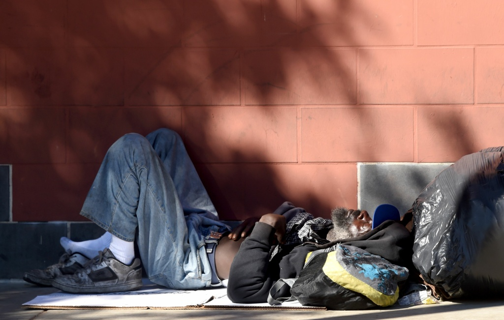 A homeless man sleeps beside the wall on the sidewalk along a street in downtown Los Angeles, California. If approved, Measure HHH could provide up to 10,000 units of permanent supportive housing for the most chronically homeless.