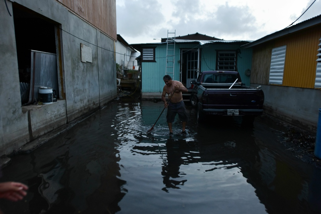 At nightfall a man tries to clean the yard next to his house damaged by Hurricane Maria in Juana Matos, Catano, Puerto Rico, on September 26, 2017.