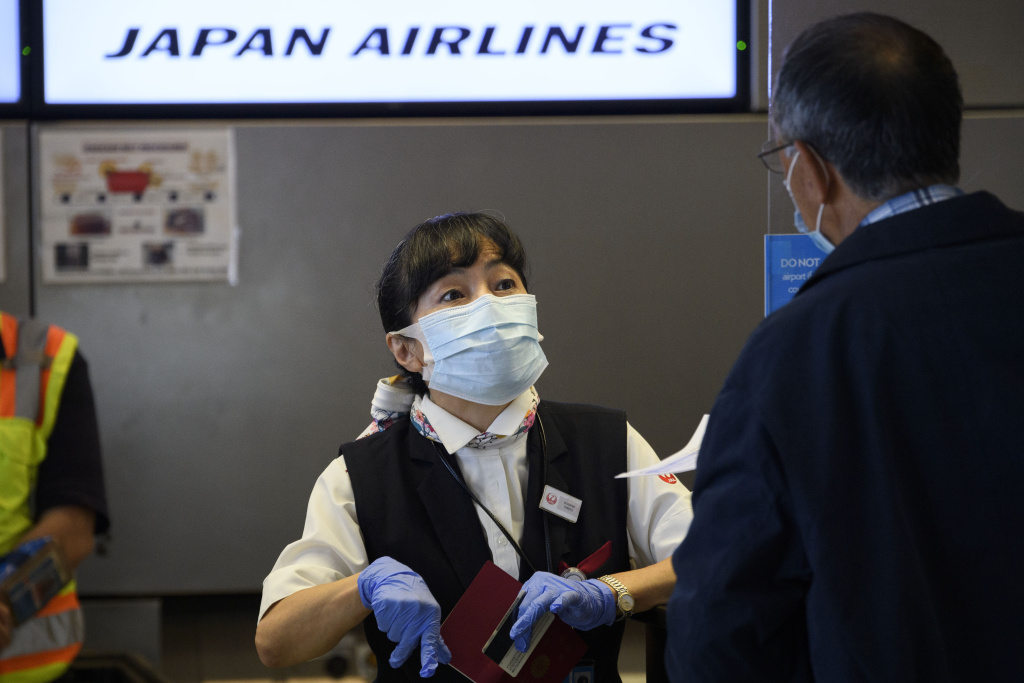 A Japan Airlines (JAL) agent checks in a passenger during the Covid-19 pandemic at Los Angeles International Airport (LAX) in Los Angeles, California, November 18, 2020.