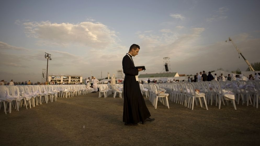 A priest prays before a Mass celebrated by Pope Benedict XVI at the Cuatro Vientos air base outside Madrid during World Youth Day festivities in August 2011.