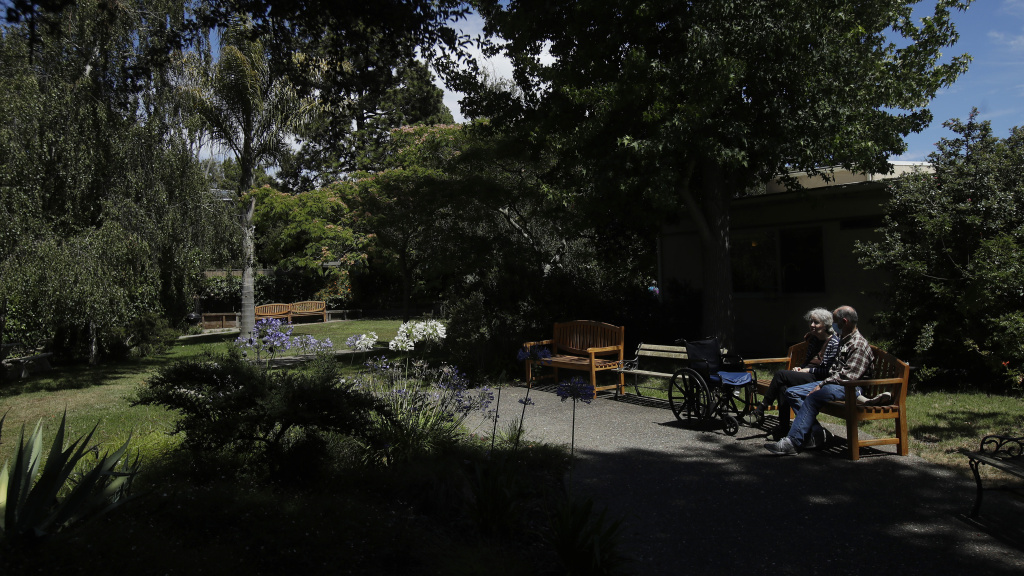 Larry Yarbroff visits his wife Mary at Chaparral House in Berkeley, Calif. in July. California health authorities had allowed some visits to resume, and now federal regulators are doing the same, with measures to try to block the spread of the coronavirus.