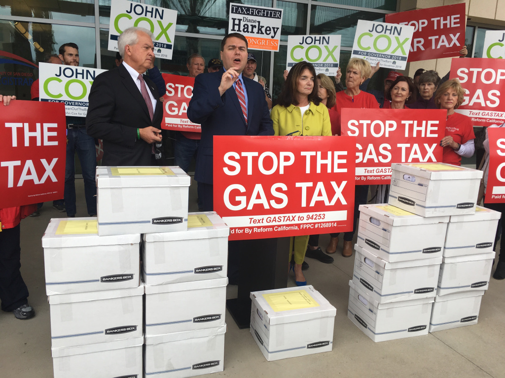 FILE: Republican gubernatorial candidate John Cox, left, and organizer Carl DeMaio, center, who led a petition drive backed by conservatives to repeal California's gas taxes and vehicle registration fees, stand Monday, April 30, 2018, in front of 15 boxes of signed petitions outside the San Diego Registrar of Voters building in San Diego before submitting them. They say 940,000 signatures were collected and should be enough to put the question on the ballot in November.