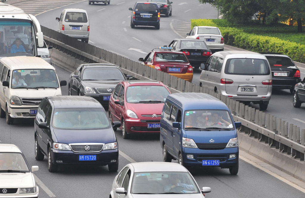 A General Motors Buick blue minivan (2/L) is seen during morning rush hour traffic along Beijing's Second Ring Road on May 14, 2009.