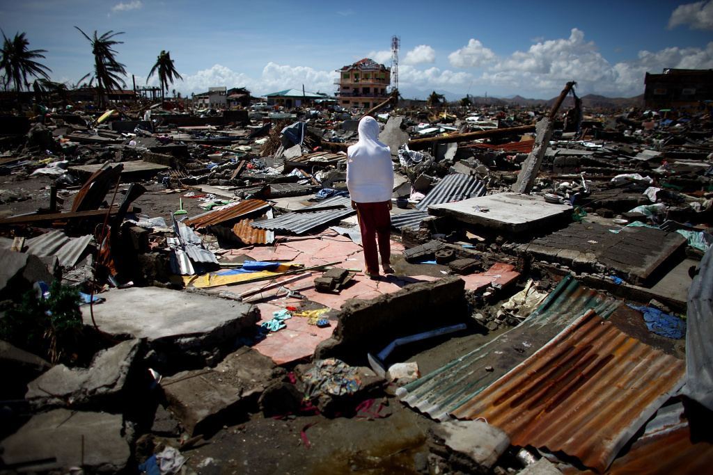 A boy stands amid ruins in Tacloban, the Philippines. The city of 220,000 was devastated by Typhoon Haiyan in 2013. To this day, the area is still trying to rebuild.