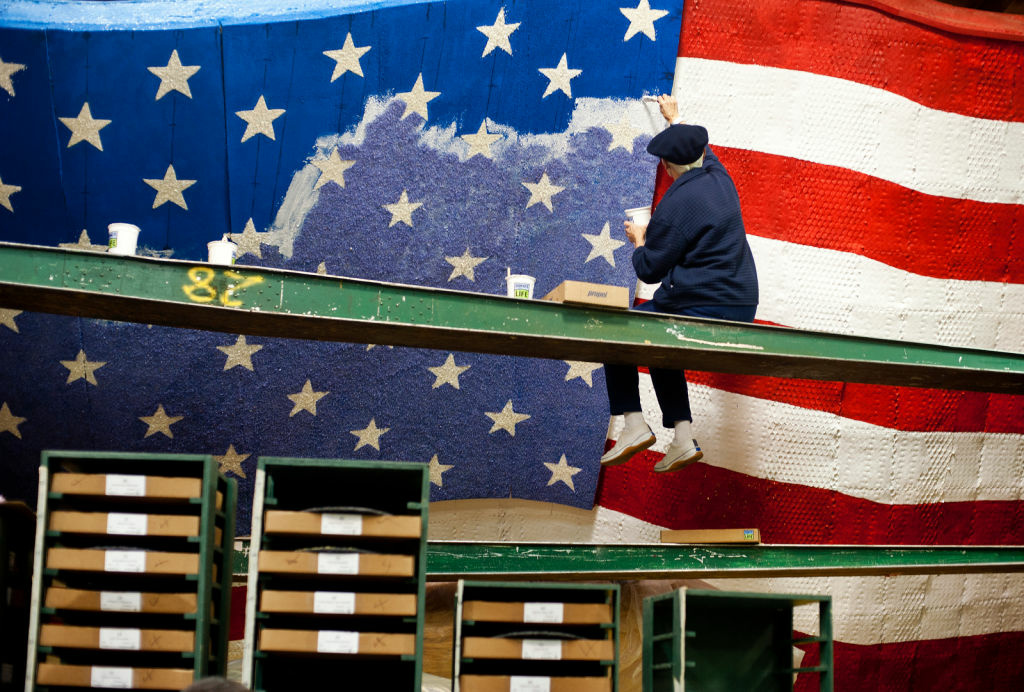 Shari Kennedy of Kiwanis International adds color to an American flag on a float in the Rosemont Pavilion on Thursday, days before the Rose Parade on New Year's Day. The float uses wheat, corn kernels, green tea leaves, parsley, and crushed split peas, among other materials, for its color.