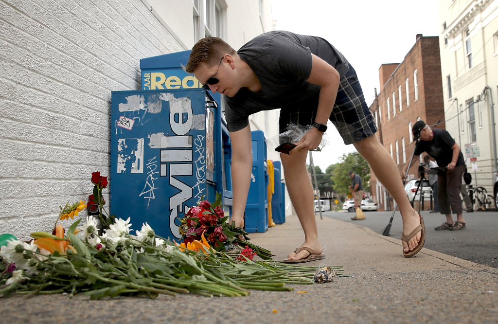 A man places flowers at a makeshift memorial for the victims of the Charlottesville attack where a car plowed into a crowd of demonstrators opposing a white supremacist rally on August 12, 2017.