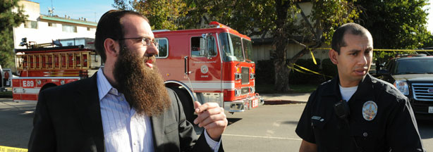 Rabbi Nachman Abend (L) waits for information outside police lines near the Adat Yeshurun Sephardic Congregation where two Jewish men were shot and injured, in Los Angeles on October 29, 2009. The two men were wounded at the Los Angeles synagogue in what police said was being investigated as a possible hate crime. Michel Moore, the deputy chief of Los Angeles police, said the two men were shot in their legs after arriving separately in an underground car park at the Adat Yeshurun Sephardic Congregation in North Hollywood.