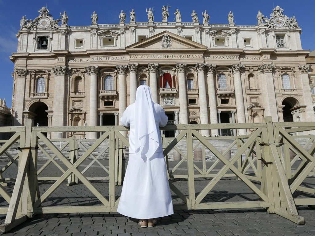 Outside Saint Peter's Basilica in Vatican City on Tuesday, a nun prays.
