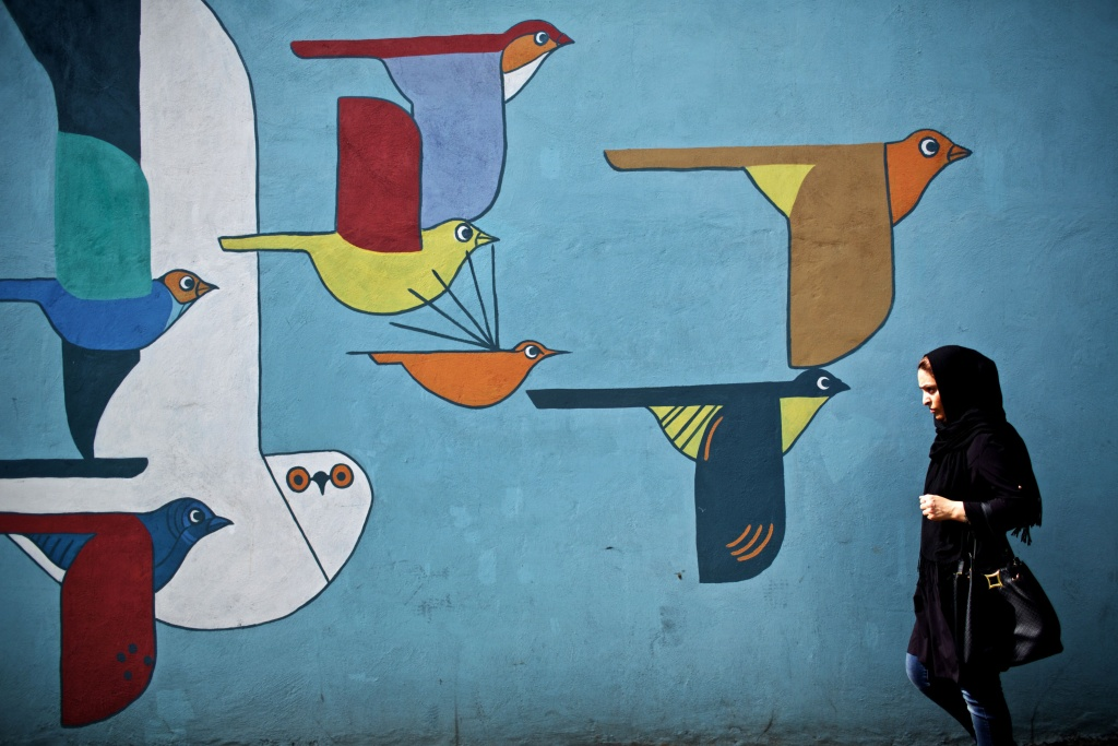 An Iranian woman walks past graffiti in a southwestern street of Tehran on June 29, 2015.